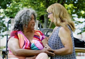 Trans activist icon Miss Major talks excitedly with a Community Pride attendee while they hold each other.