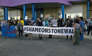 """A crowd of protesters hold a large white banner with black texts that reads """"#ShameOnStonewall."""""""