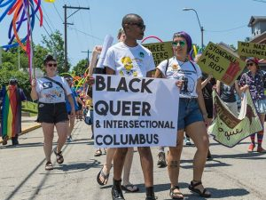 """A colorful protest march led by two activists carrying a """"Black Queer & Intersectional Columbus"""" sign."""